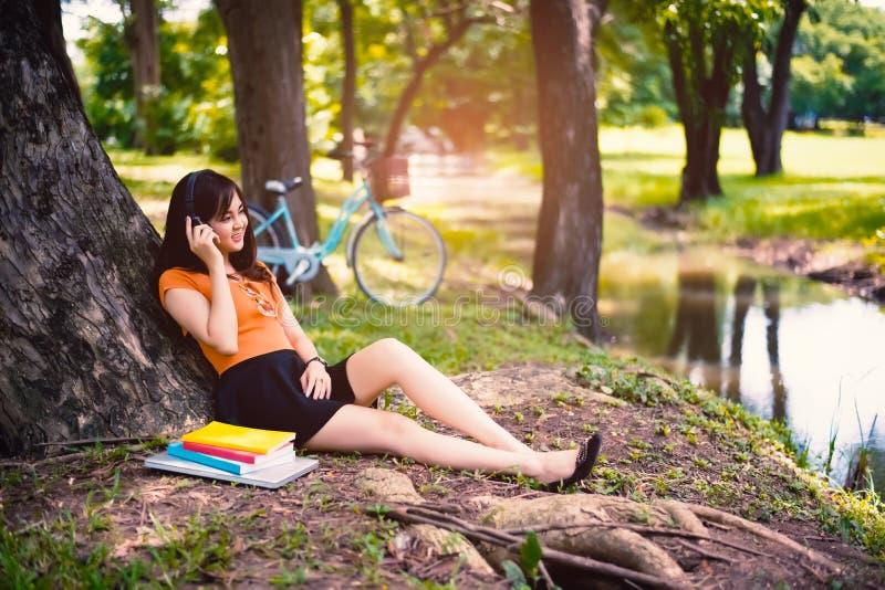 Frau entspannen sich unter dem Baum im Park mit Kopfhörern, sich entspannen Konzept stockfotografie