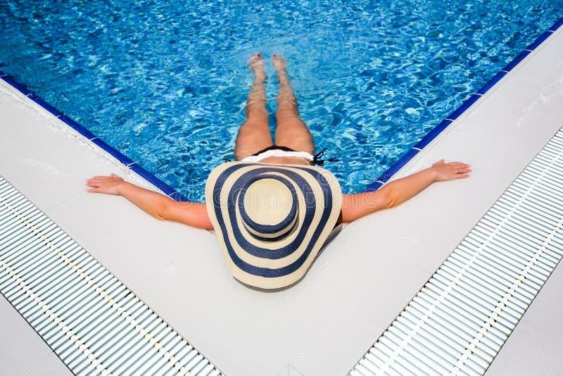 Frau in entspannendem Swimmingpool des Strohhutes lizenzfreie stockbilder