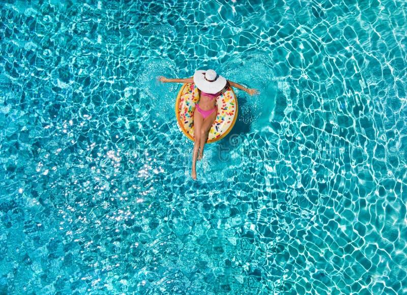 Frau entspannt sich auf einem ringförmigen Floss über blauem, funkelndem Poolwasser stockfotos