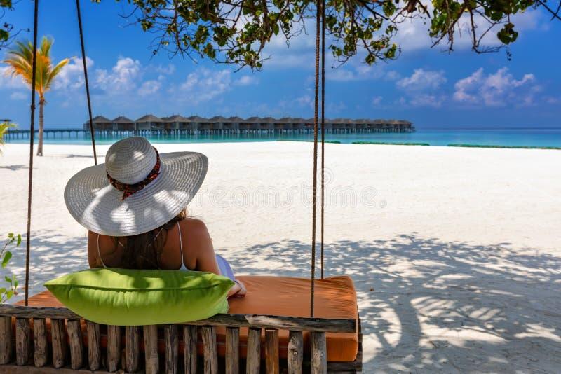 Frau entspannt sich auf einem Schwingen in den Malediven-Inseln stockfotografie
