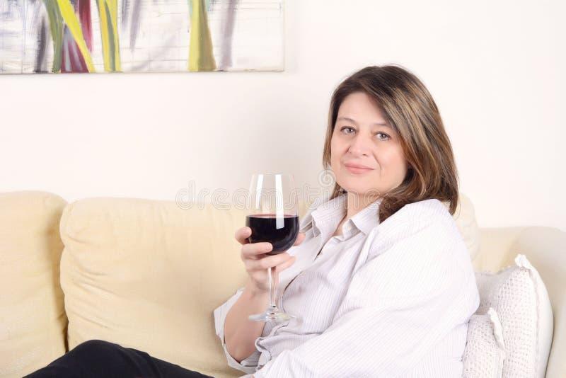 Frau entspannte sich auf Sofa mit einem Glas Wein lizenzfreies stockbild