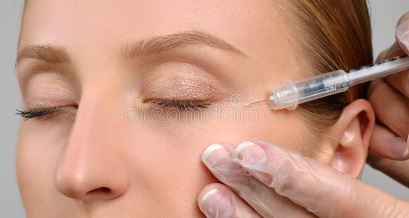 Frau erhält botox Einspritzung Anti-Alternbehandlung und Facelift Kosmetische Behandlung und plastische Chirurgie lizenzfreies stockfoto