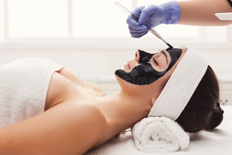 Frau erhält Gesichtsmaske durch Kosmetiker am Badekurort lizenzfreies stockfoto
