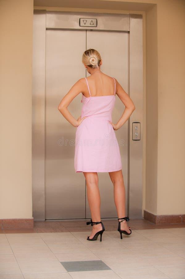 Frau erwartet Aufzugankunft lizenzfreies stockbild