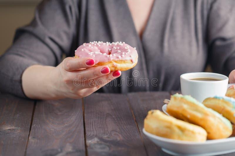Frau essen Donut und trinken Kaffee stockbilder