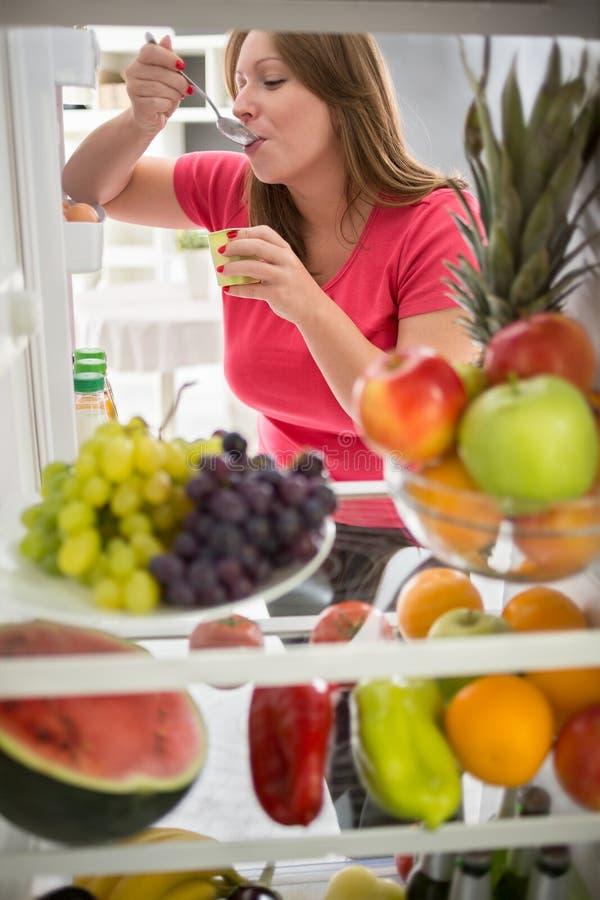Frau essen Fruchtjoghurt vom Kühlschrank lizenzfreie stockbilder