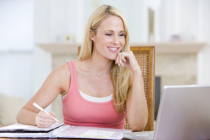 Frau in Esszimmer mit dem Laptoplächeln stockbilder