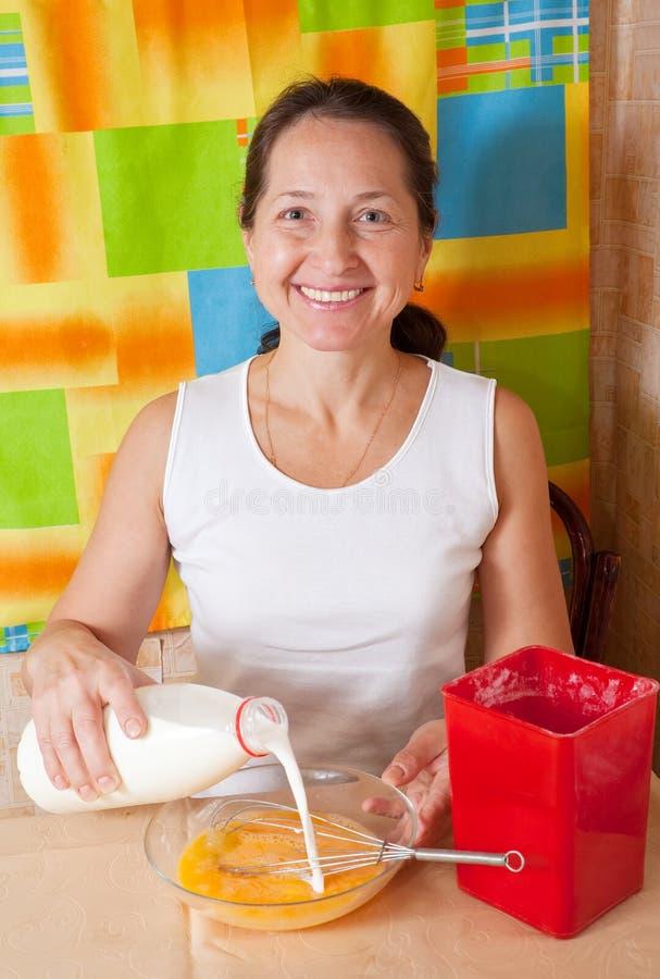 Frau fügt Milch in Teller hinzu stockfoto