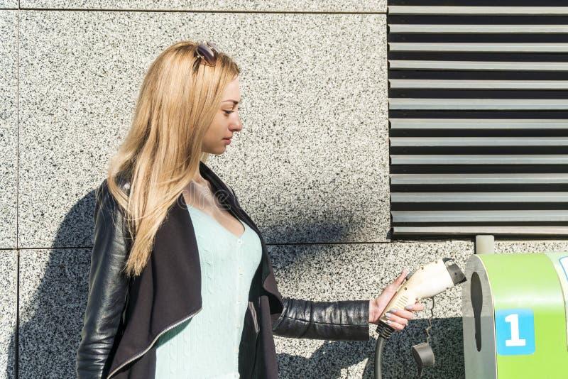Frau fügt Verbindungsstück in Ladestation ein lizenzfreies stockfoto