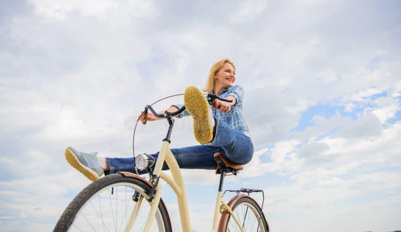 Frau fühlt sich frei, während genießen Sie radzufahren Mädchen reitet Fahrradhimmelhintergrund Die meiste befriedigende Form des  stockbilder
