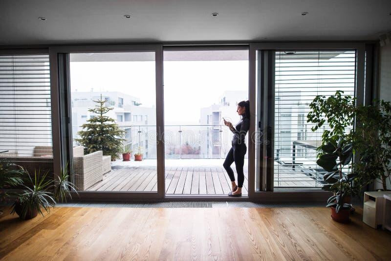 Frau am Fenster mit Smartphone, Versenden von SMS-Nachrichten lizenzfreie stockfotografie