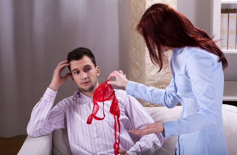 Frau findet jemand Unterwäsche nahe Ehemann stockfoto