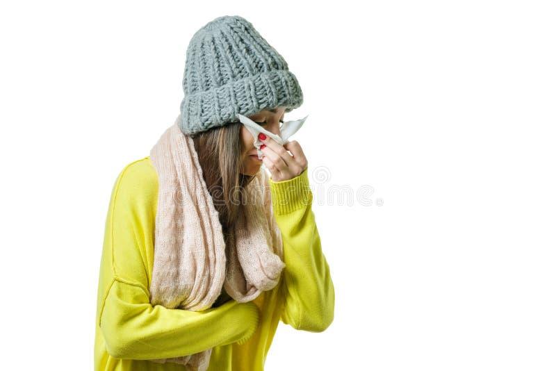 Frau fing eine Kälte im warmen Hut und im Schal mit dem Taschentuch, lokalisiert auf weißem Hintergrund, Grippe-Saison lizenzfreie stockfotos