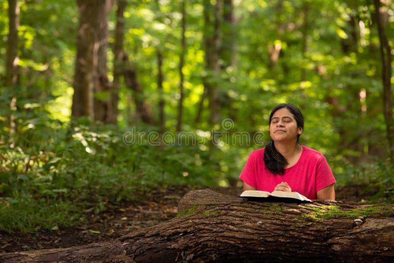 Frau in Forest Preserve mit Bibel kniend im Gebet stockbilder