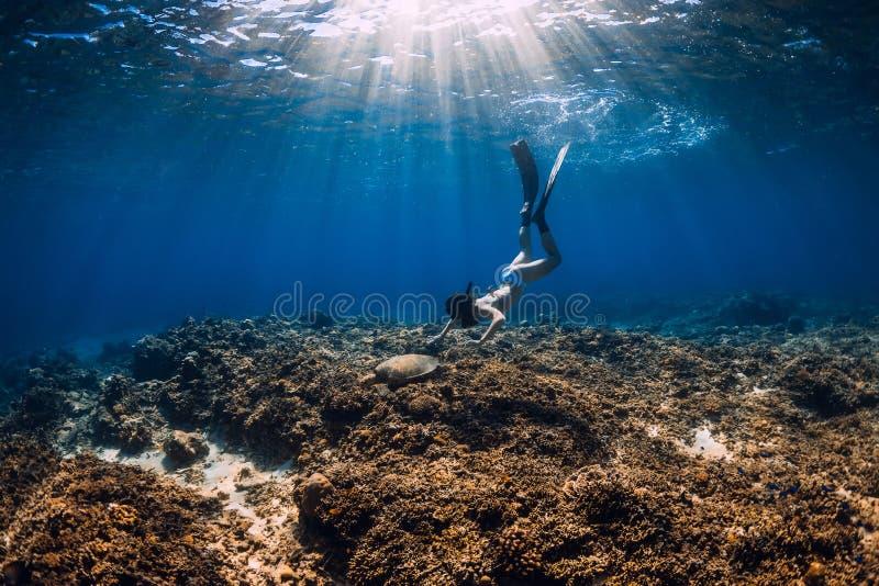 Frau freediver gleitet über Riffunterseite mit Flossen und Schildkröte lizenzfreies stockfoto