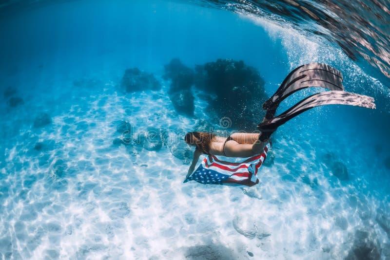 Frau freediver gleitet über sandigem Meeresgrund mit Flagge Vereinigter Staaten lizenzfreie stockbilder