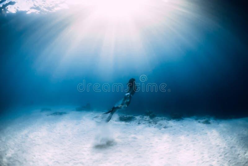 Frau freediver im Bikini über sandigem Meer mit Flossen Freediving Unterwasser stockfotografie