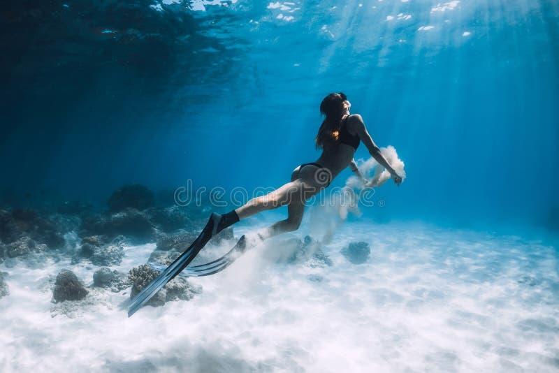 Frau freediver Schwimmen Unterwasser über sandiger Unterseite mit Sand stockbild