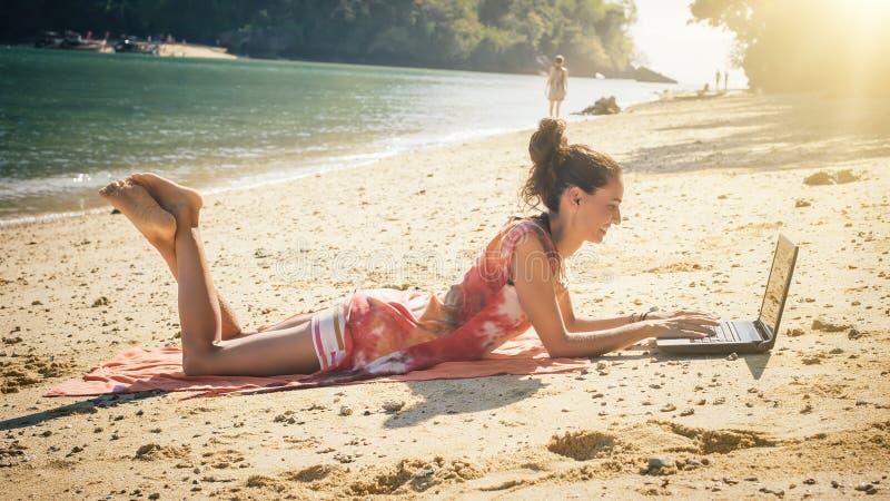 Frau freiberuflich tätig auf Laptop-Computer am tropischen, exotischen Strand stockfotografie