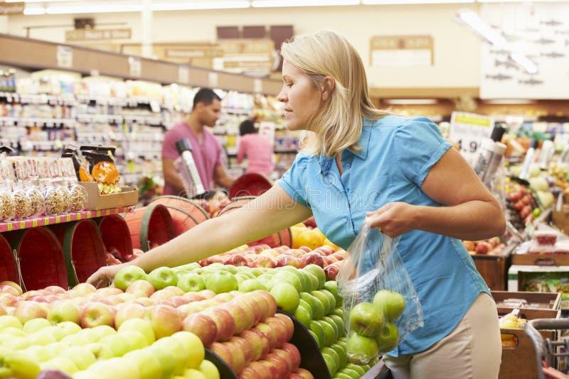 Frau am Frucht-Zähler im Supermarkt lizenzfreie stockfotos