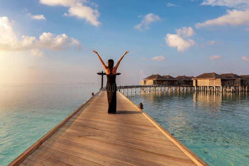 Frau geht auf eine hölzerne Anlegestelle in den Malediven lizenzfreies stockfoto