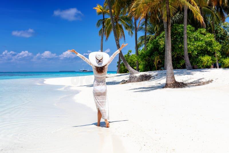 Frau geht auf einen tropischen Strand mit weißem Hut stockfoto