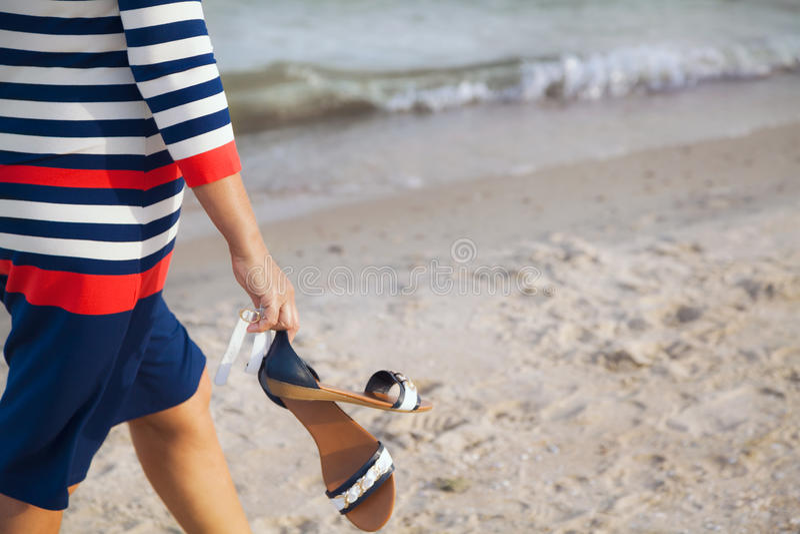 Frau geht entlang sandigen Strand stockfotografie