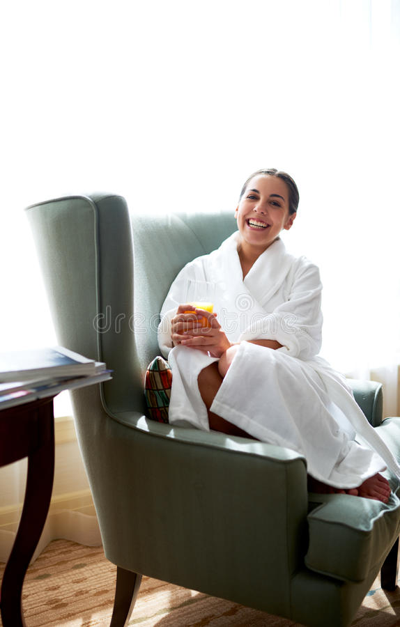 Frau gekräuselt oben im Stuhl, der weit lächelt stockbild