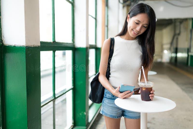Frau genießen gefrorenen Kaffee und Haltenmobiltelefon im Freilichtcafé lizenzfreie stockfotos