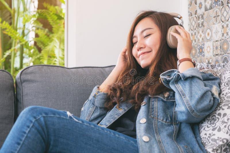 Frau genießen, Musik mit Kopfhörer mit dem Gefühl zu hören, das glücklich und im Café entspannt ist stockbild