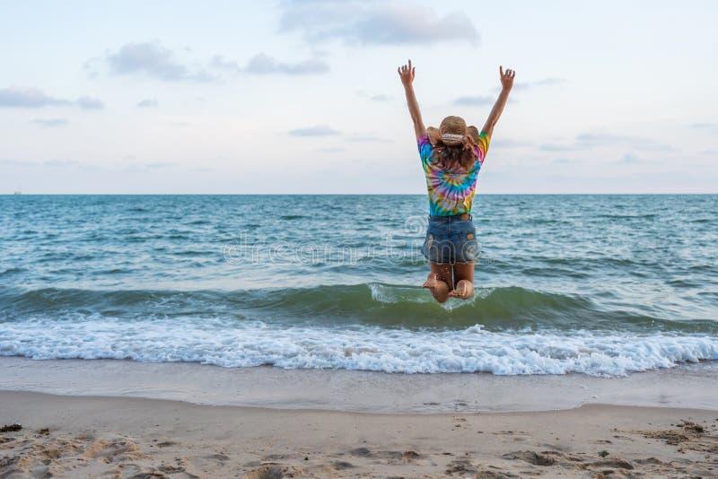 Frau genießen und springend auf Seestrand stockbilder