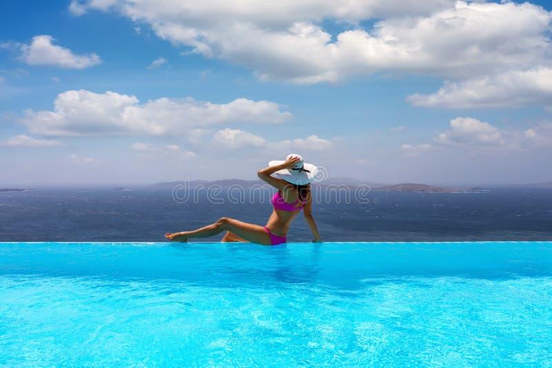 Frau genießt die Ansicht vom Pool zum Mittelmeer lizenzfreie stockbilder