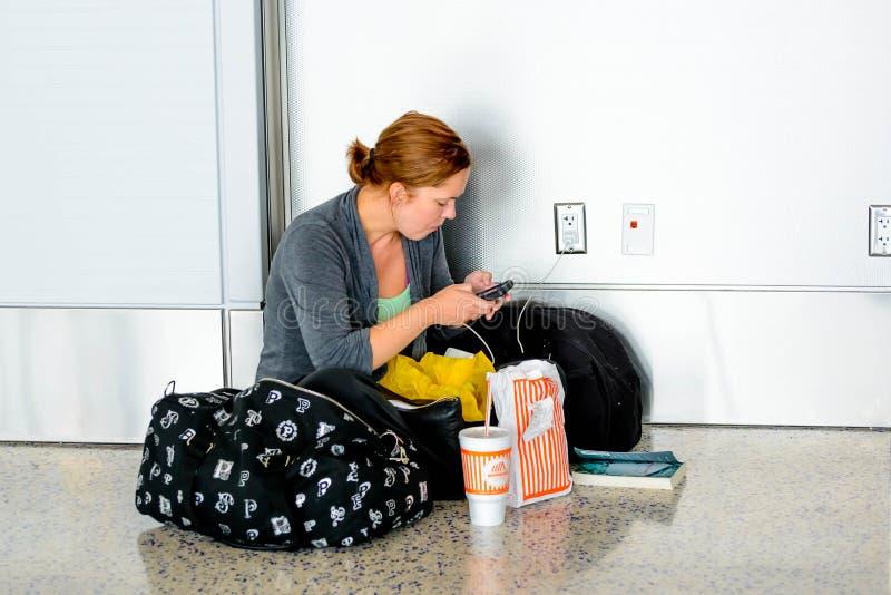 Frau gesetzt auf dem Boden, der ihr Telefon in einem Flughafen auflädt stockfotos