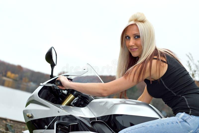 Frau gesetzt auf einem Motorrad stockfotos