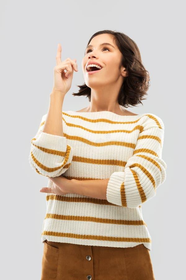 Frau in gestreiftem Pullover ihren Finger oben zeigend lizenzfreies stockfoto