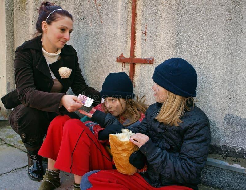 Frau gibt den Kindbettlern Geld lizenzfreie stockfotografie