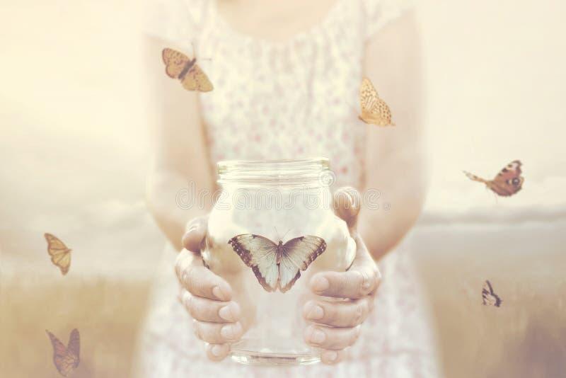Frau gibt einigen Schmetterlingen Freiheit, die in einem Glasvase eingeschlossen werden stockbild