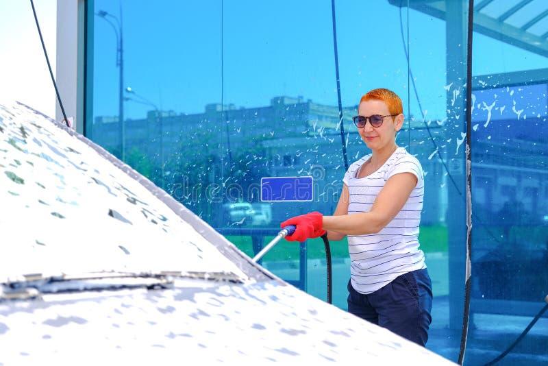Frau gießt aktive Schaumfahrzeugkarosserie Autowashington-saubere Maschine, Autow?sche mit Schwamm und Schlauch Selbstbedienungsr stockbilder