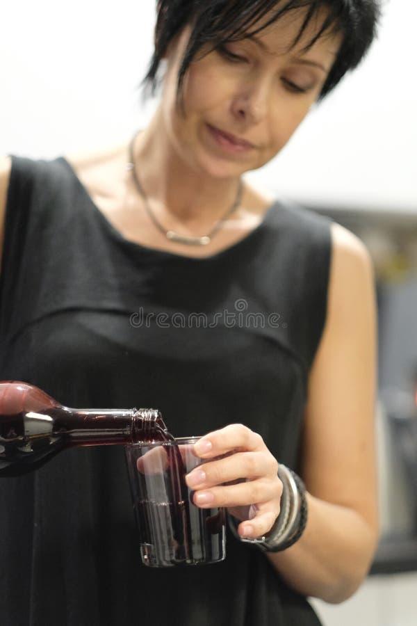 Frau gießt in ein Glas Saft stockbilder