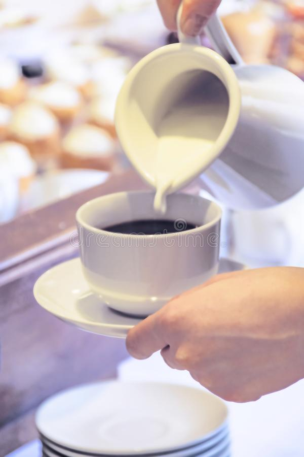 Frau gießt Milch in einen Tasse Kaffee, der einen Becher und eine Untertasse über der Tabelle hält Kaffee-Cateringe in einem Hote stockbild