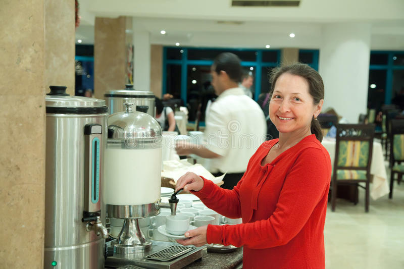 Frau gießt Milch zum Kaffee stockfoto