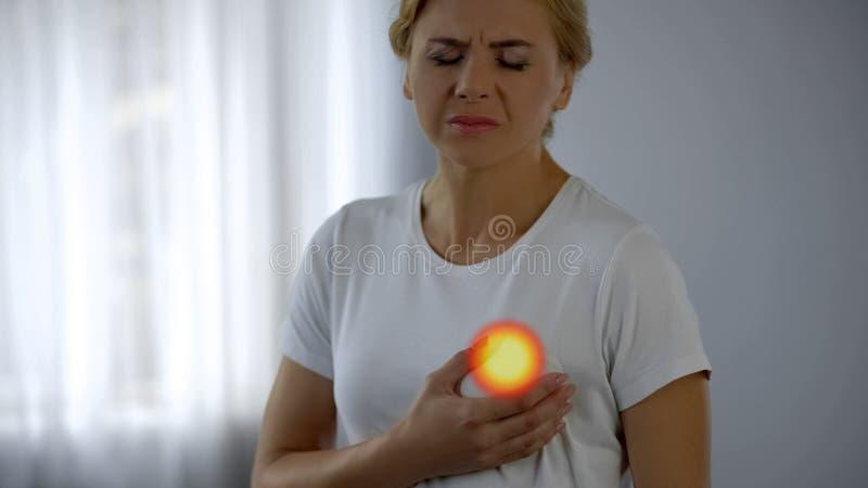 Frau glaubt den Schmerz in der Brust und überprüft Milch- Drüse, Engesymptome von Krebs lizenzfreie stockfotos