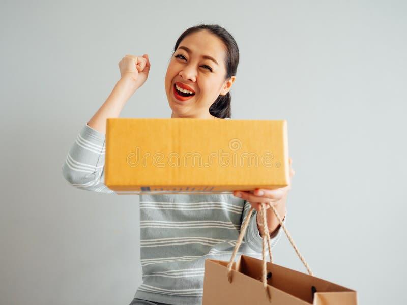 Frau glaubt gl?cklich und mit dem on-line purchursed ?berrascht stockbild