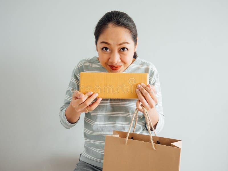 Frau glaubt gl?cklich und mit dem on-line purchursed ?berrascht stockfotografie