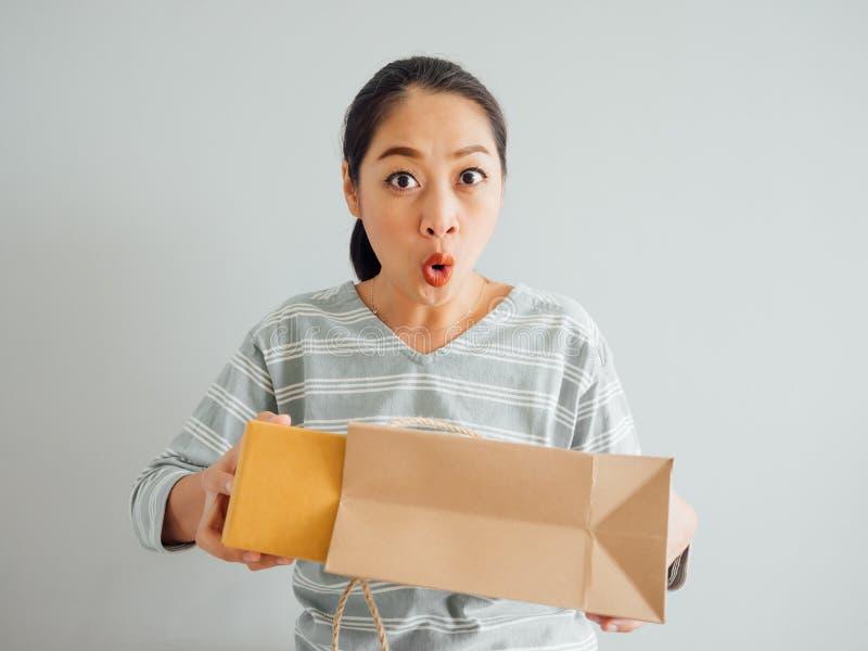 Frau glaubt gl?cklich und mit dem on-line purchursed ?berrascht lizenzfreies stockfoto