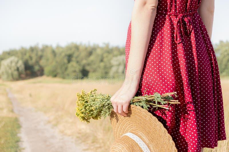 Frau hält Bündel von Feldblumen und von Hut im rustikalen Hintergrund lizenzfreie stockfotos
