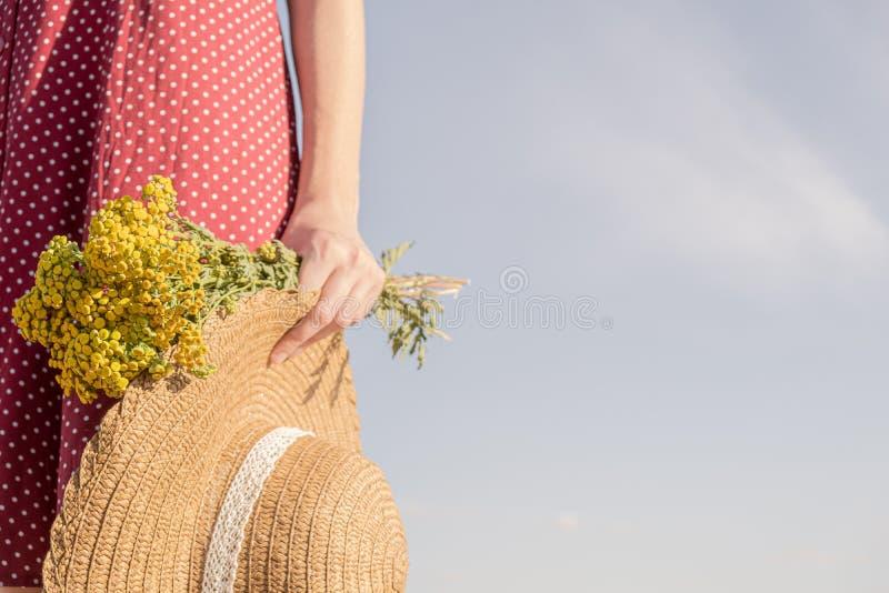 Frau hält Bündel von Feldblumen und von Hut stockbilder
