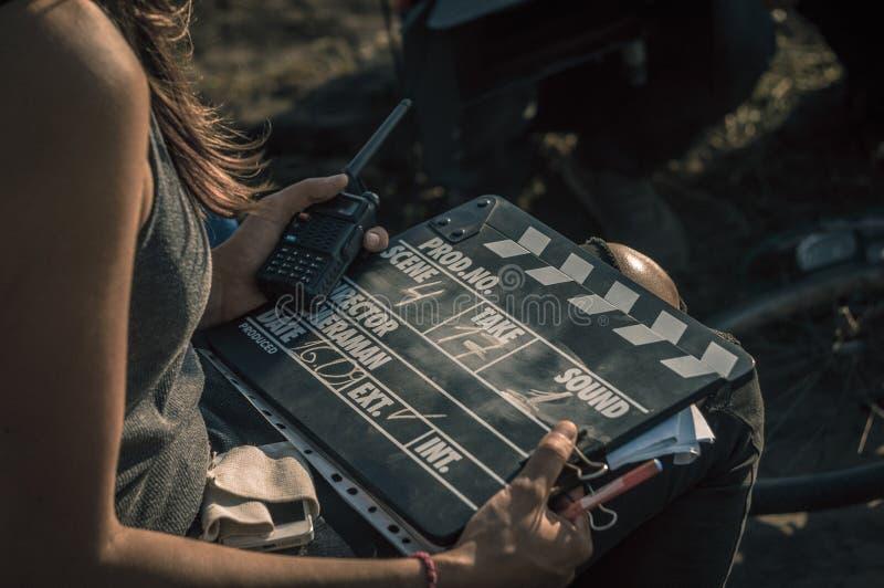 Frau hält Clapperboard und Funksprechgerät lizenzfreie stockfotografie