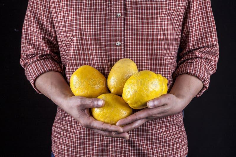 Frau hält ein Bündel Zitronen lizenzfreie stockbilder