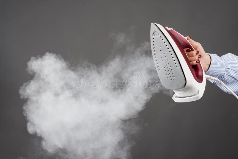 Frau hält ein Eisen mit Dampf auf grauem Hintergrund lizenzfreies stockfoto
